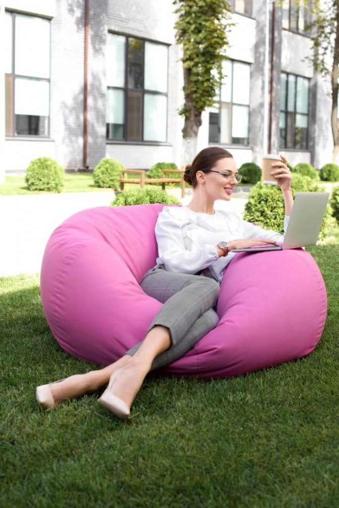A hiring manager lazing in the office garden on a bright pink bean bag