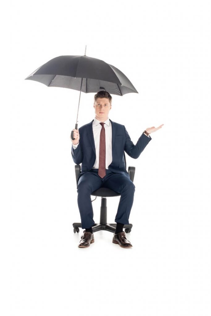 A man in a business suit sitting on an office chair holding an umbrella - will this rain stop Adria? No it won't!